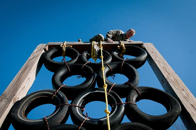 Man scaling a barrier on an assault course