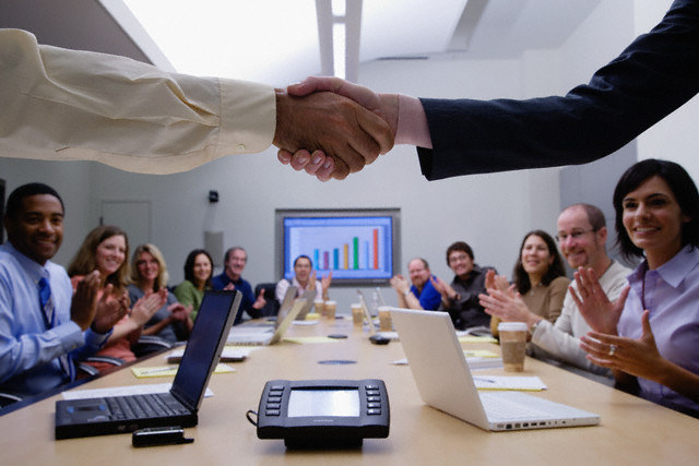 Two people shaking hands in a meeting