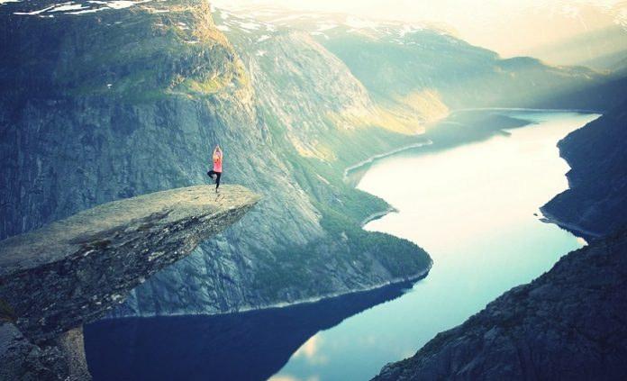 A person doing yoga poses on a cliff