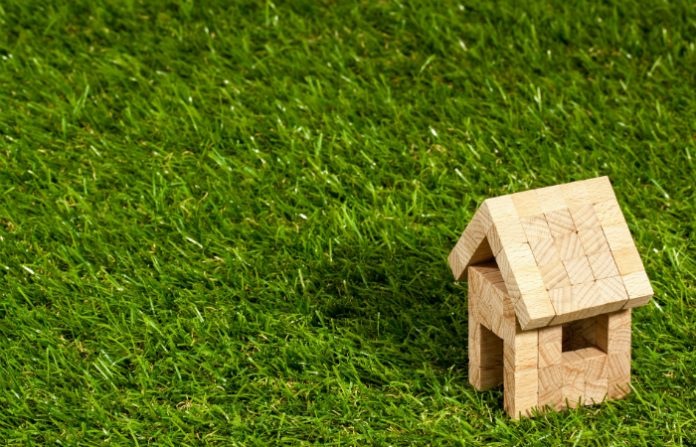 toy wooden house on some grass